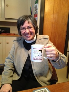 The Rev. Anne Emry drinking coffee in Tim's office out of her 2013 mug.